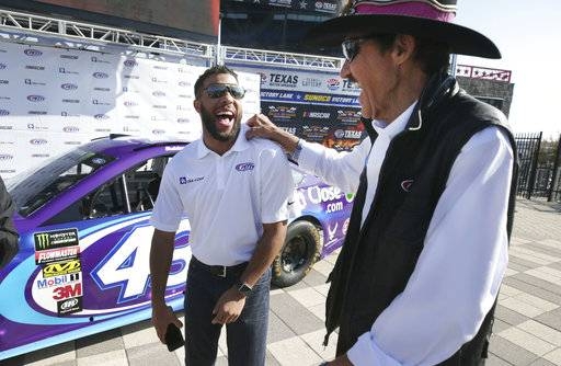 Darrell Wallace Jr., left, laughs with Richard Petty after unveiling the paint scheme for Wallace's car before NASCAR Cup series auto race qualifying at Texas Motor Speedway in Fort Worth, Texas, Friday, Nov. 3, 2017. Richard Petty Motorsports announced that Wallace Jr. will drive the No. 43 car for the organization beginning in 2018. (AP Photo/LM Otero)