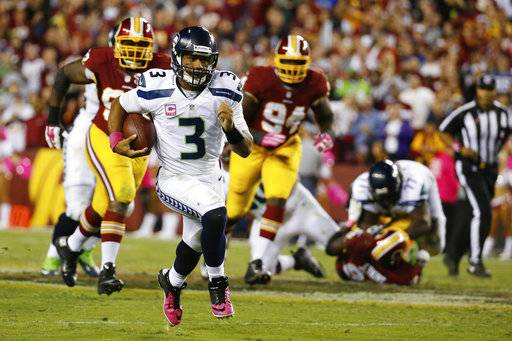 FILE - In this Oct. 6, 2014, file photo, Seattle Seahawks quarterback Russell Wilson (3) scrambles with the ball during the second half of an NFL football game against the Washington Redskins in Landover, Md. After being tormented by Carson Wentz and Dak Prescott, the Redskins' bruised and battered defense faces another test from a mobile quarterback against the Seahawks' Russell Wilson. (AP Photo/Alex Brandon, File)