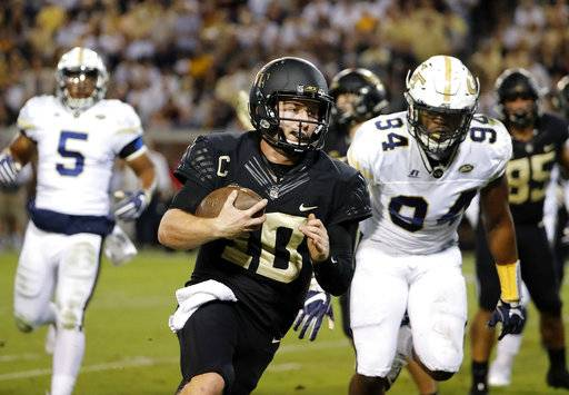FILE - In this Saturday, Oct. 21, 2017, file photo, Wake Forest quarterback John Wolford runs the ball for a touchdown in the second quarter of an NCAA college football game against Georgia Tech in Atlanta. Notre Dame coach Brian Kelly can deal with Saturday afternoon's reunion of defensive assistants Mike Elko and Clark Lea with their former Wake Forest boss Dave Clawson. Whether Kelly's No. 5 Irish can deal on the field with the explosive 5-3 Blue Demons, fresh off a 42-32 victory against Louisville, is another matter. (AP Photo/David Goldman, File)