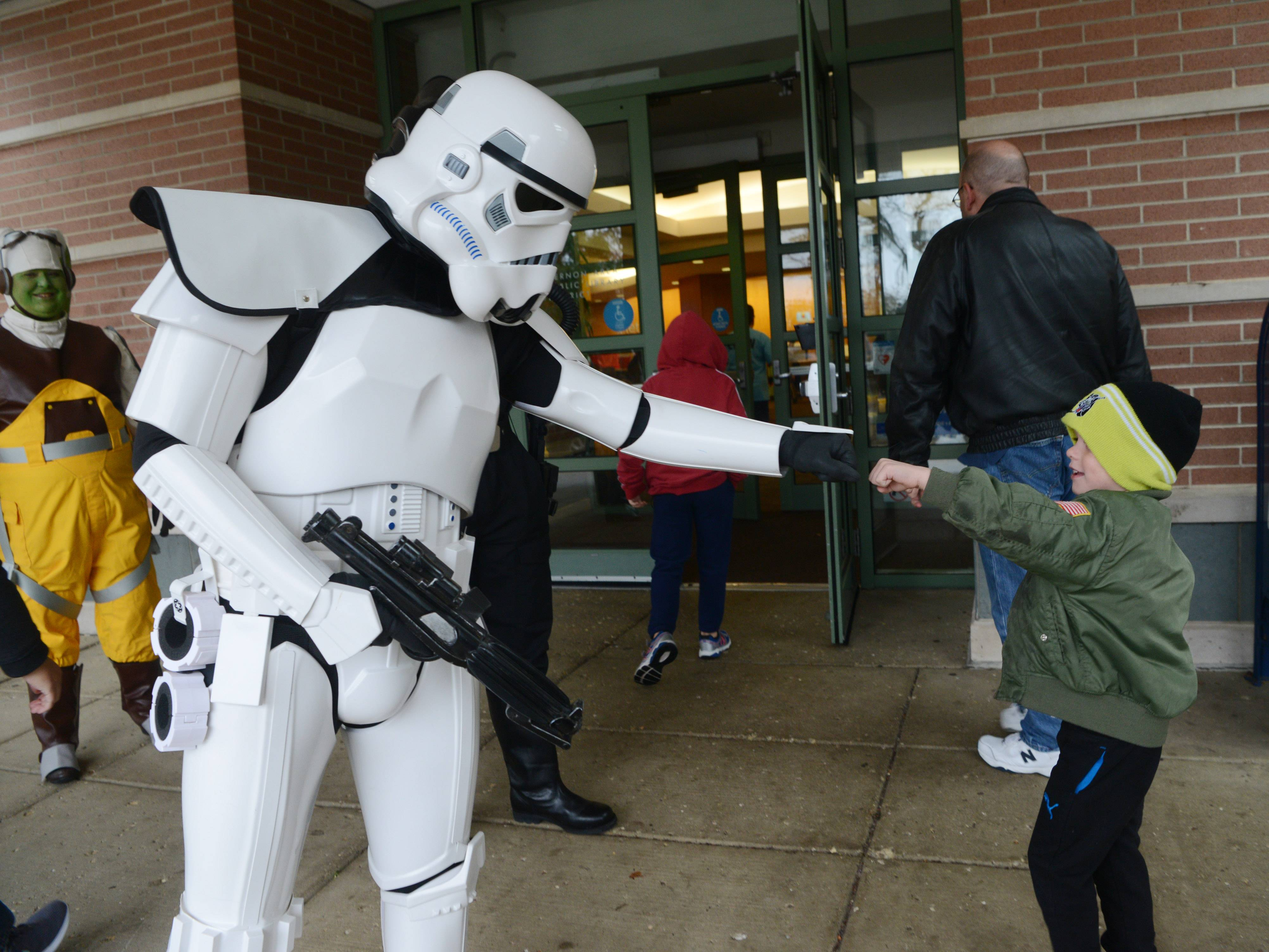"William Dionne, 5, of Gurnee is greeted by a ""Star Wars"" storm trooper outside the fourth annual Mini Comic Con at the Vernon Area Public Library in Lincolnshire Saturday."