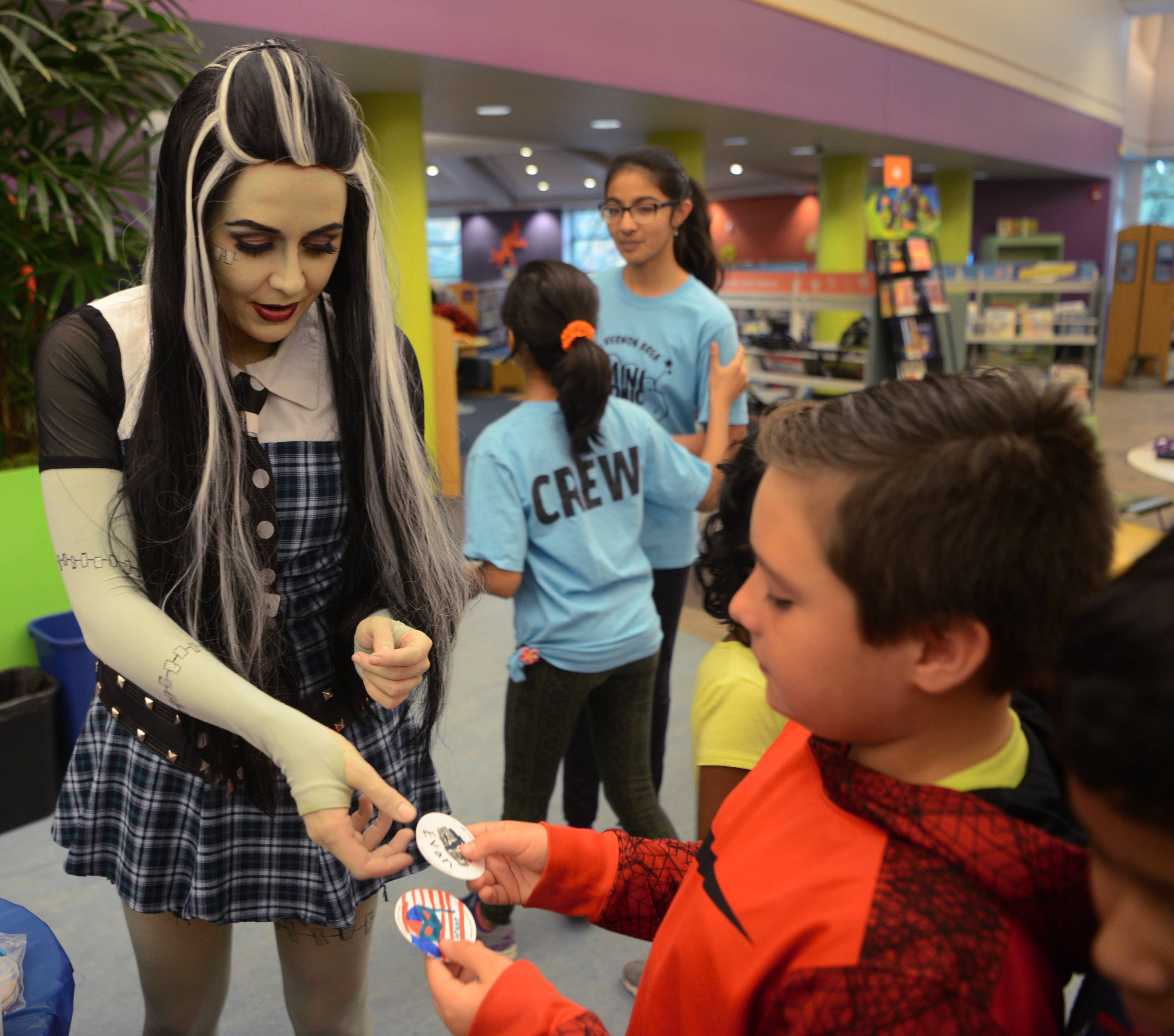 "Jessica Flor, a library program coordinator dressed as Frankie Stein from ""Monster High,"" makes buttons for kids, including Grant Torres, 8, of Vernon Hills during the fourth annual Mini Comic Con at the Vernon Area Public Library in Lincolnshire Saturday."