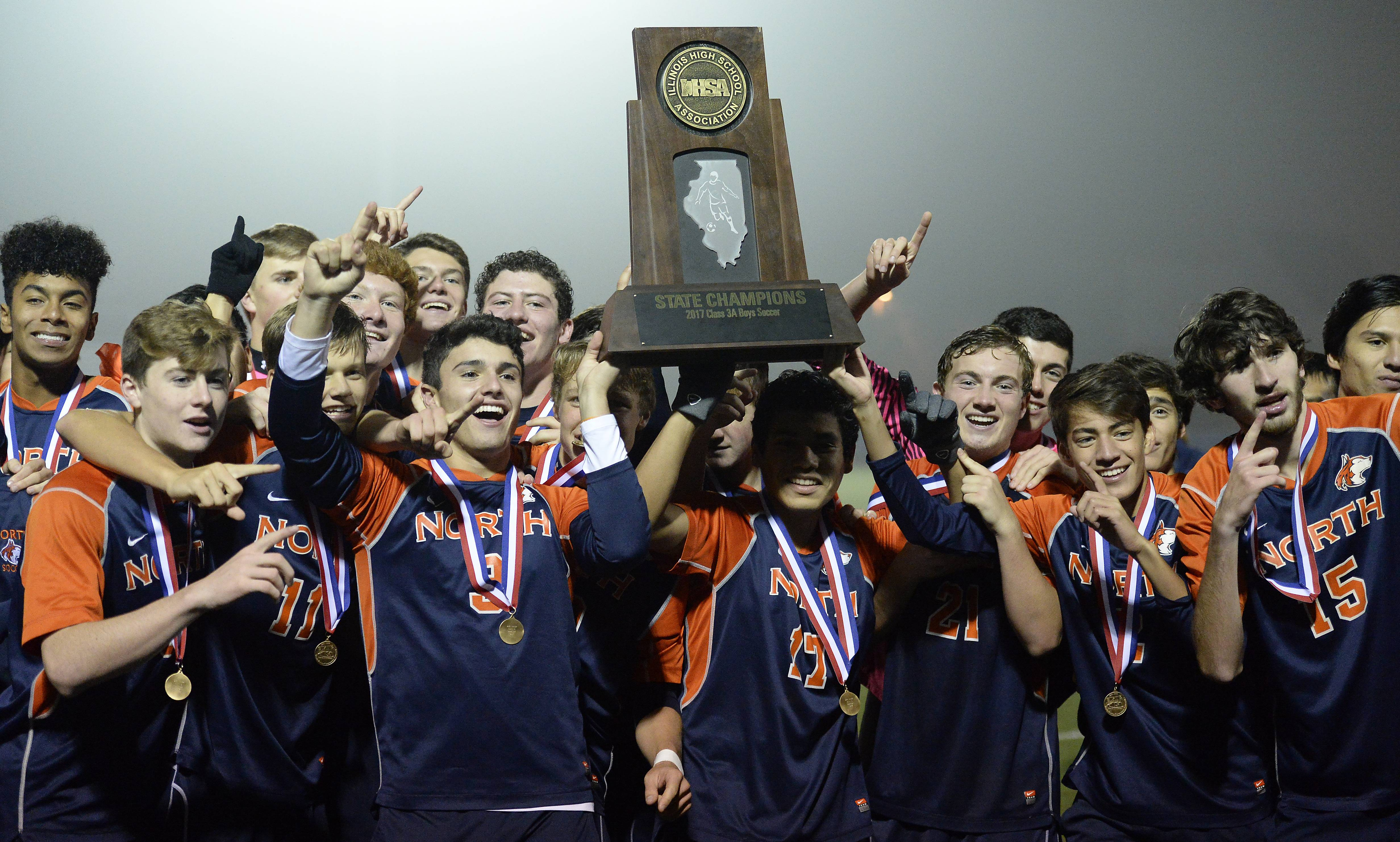 Naperville North's soccer team players hold up their first place trophy after beating Libertyville 1-0 in the state soccer championship game at Hoffman Estates.
