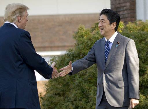 President Donald Trump, left, greets Japanese Prime Minister Shinzo Abe at Kasumigaseki Country Club, Sunday, Nov. 5, 2017, in Kawagoe, Japan. Trump is on a five country trip through Asia traveling to Japan, South Korea, China, Vietnam and the Philippines.
