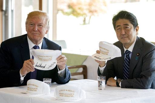 "President Donald Trump and Japanese Prime Minister Shinzo Abe hold up hats they have both signed that read ""Donald and Shinzo, Make Alliance Even Greater"" at Kasumigaseki Country Club, Sunday, Nov. 5, 2017, in Kawagoe, Japan. Trump is on a five country trip through Asia traveling to Japan, South Korea, China, Vietnam and the Philippians."