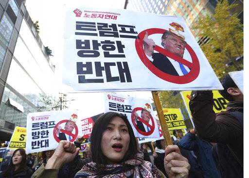 "A protester shouts slogans during a rally to oppose a planned visit by U.S. President Donald Trump in Seoul, South Korea, Saturday, Nov. 4, 2017. The signs read ""We oppose Trump's visit."""
