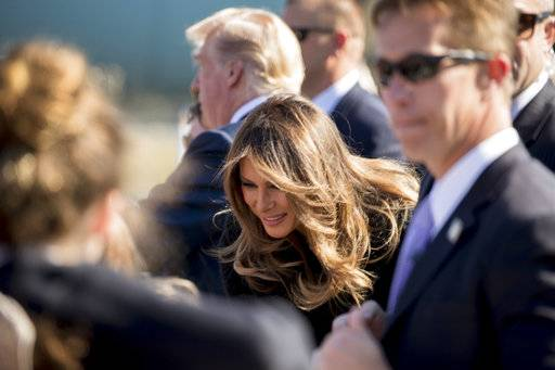 First lady Melania Trump, center, and President Donald Trump, background, greet guest on the tarmac as they arrives at Yokota Air Base, Sunday, Nov. 5, 2017, in Fussa, on the outskirts of Tokyo, Japan. Trump is on a five country trip through Asia traveling to Japan, South Korea, China, Vietnam and the Philippines.