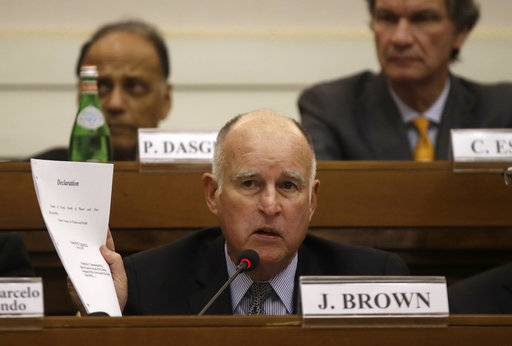 "California Gov. Jerry Brown shows a paper during a workshop organized by Vatican on the climate change, at the Casina Pio IV, at the Vatican, Saturday Nov.4, 2017. Brown called climate change an existential threat and said he's going to announce in Bonn that more signatories will be joining the ""Under2 coalition"" a global community committed to decarbonization and supporting the Paris Agreement's climate goal of keeping the rise in global average temperatures below 2 degrees centigrade."