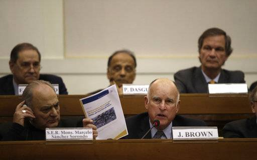 "California Gov. Jerry Brown, front, right, flanked by Minsignor Marcelo Sorondo, shows a paper during a workshop organized by Vatican on the climate change, at the Casina Pio IV, at the Vatican, Saturday Nov.4, 2017. Brown called climate change an existential threat and said he's going to announce in Bonn that more signatories will be joining the ""Under2 coalition"" a global community committed to decarbonization and supporting the Paris Agreement's climate goal of keeping the rise in global average temperatures below 2 degrees centigrade."