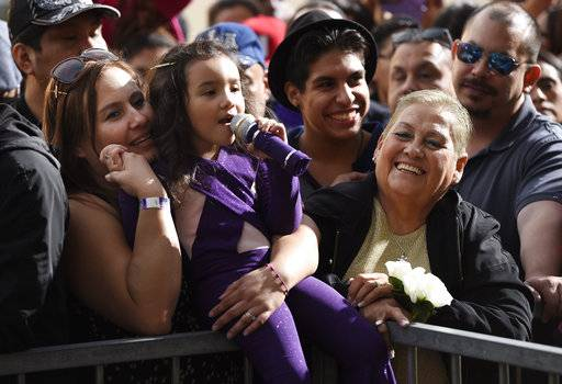Sammi Corono-Lampa, 4, of Moreno Valley, Calif., a fan of the late singer Selena Quintanilla, sings songs by Quintanilla as she waits with her mother Patty, left, and her grandmother, Teresa, for a posthumous star ceremony on the Hollywood Walk of Fame on Friday, Nov. 3, 2017, in Los Angeles. (Photo by Chris Pizzello/Invision/AP)