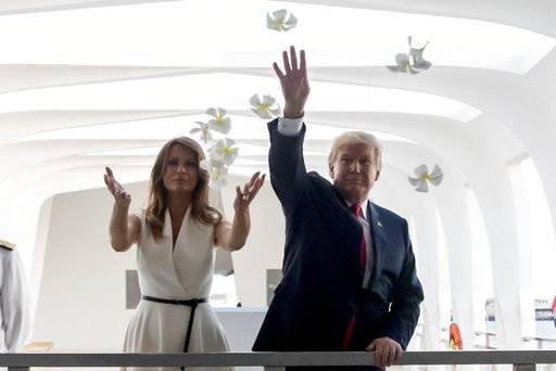 U.S. President Donald Trump and first lady Melania Trump throw flower pedals while visiting the Pearl Harbor Memorial in Honolulu, Hawaii Friday, Nov. 3, 2017. Trump paid a solemn visit Friday to Pearl Harbor and its memorial to the USS Arizona, a hallowed place he said he had read about, discussed and studied but had never visited until just before opening his first official visit to Asia.