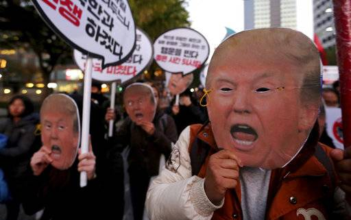 "Protesters wearing masks of U.S. President Donald Trump march toward the U.S. Embassy during a rally to oppose a planned his visit in Seoul, South Korea, Saturday, Nov. 4, 2017. The signs read "" Stop the War."""