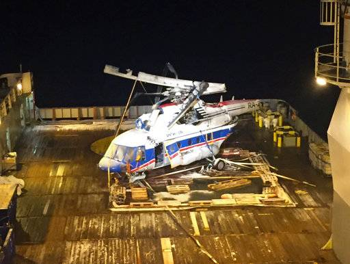 In this photo provided by The Accident Investigation Board Norway, the body, rotor and separated tail of the helicopter MI-8AMT with the registration RA-22312 is lifted up on deck of the ship Maersk Forza, off the coast of Svalbard, Norway, early Saturday, Nov. 4, 2017. A Russian helicopter that crashed off Norway's Arctic Svalbard archipelago with eight people onboard last month has been raised from the seabed.  Norway's Accident Investigation Board says none of the missing people were inside the helicopter that went down Oct. 26 near the Svalbard settlement of Barentsburg. (The Accident Investigation Board Norway via AP)