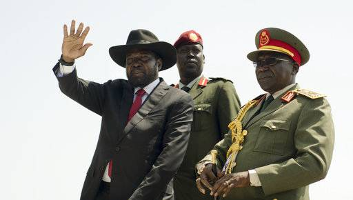 FILE - In this Thursday, July 9, 2015, file photo, South Sudan's President Salva Kiir, left, accompanied by then army chief of staff Paul Malong, right, waves during an independence day ceremony in the capital Juba, South Sudan. Tensions are high Saturday, Nov. 4, 2017, in Juba after President Salva Kiir sent troops to surround the home of former military chief of staff Paul Malong, disarm his bodyguards and remove all weapons.
