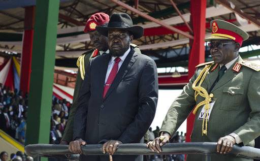 FILE - In this Thursday, July 9, 2015, file photo, South Sudan's President Salva Kiir, center, is accompanied by then army chief of staff Paul Malong, right, as they attend an independence day ceremony in the capital Juba, South Sudan. Tensions are high Saturday, Nov. 4, 2017, in Juba after President Salva Kiir sent troops to surround the home of former military chief of staff Paul Malong, disarm his bodyguards and remove all weapons.