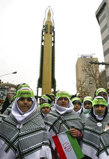 Iranian children attend an annual gathering in front of the former U.S. Embassy marking the anniversary of its 1979 takeover, while a surface-to-surface Sejjil missile is displayed by the Revolutionary Guard, at rear, in Tehran, Iran, Saturday, Nov. 4, 2017. Iran on Saturday displayed a surface-to-surface missile as part of events marking the anniversary of the 1979 U.S. Embassy takeover and hostage crisis amid uncertainty about its nuclear deal with world powers.