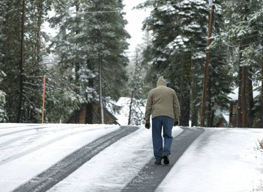 A man walks a snow covered road near Soda Springs, Calif., Friday, Nov. 3, 2017. A light snow fell in the upper elevations of the Sierra Nevada overnight, with up to 2 feet of snow forecast to fall in elevations above 8,000 feet and at least a foot of snow is expected in Donner and Tioga passes and other areas above 6,000 feet and up this weekend, forecasters said.