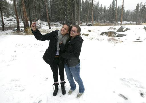Emily, left, and her sister Stephanie pose for a selfie in the snow at a rest stop Friday, Nov. 3, 2017, at Donner Summit, Calif. A light snow fell in the upper elevations of the Sierra Nevada overnight, with up to 2 feet of snow forecast to fall in elevations above 8,000 feet and at least a foot of snow is expected in Donner and Tioga passes and other areas above 6,000 feet and up this weekend, forecasters said.