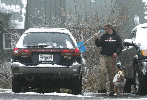 Brad Moran, accompanied by his dog, Sonny, removes snow from his car Friday, Nov. 3, 2017, at Donner Summit, Calif. A light snow feel in the upper elevations of the Sierra Nevada overnight, with up to 2 feet of snow forecast to fall in elevations above 8,000 feet and at least a foot of snow is expected in Donner and Tioga passes and other areas above 6,000 feet and up this weekend, forecasters said.