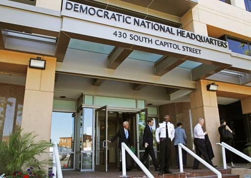 FILE - In this June 14, 2016 file photo, people stand outside the Democratic National Committee headquarters in Washington. Hackers tried to break into DNC inboxes in March 2016 and intensified their efforts in early April.