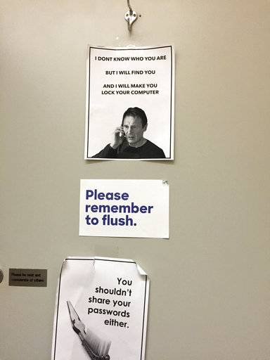 This June 29, 2016 photo shows signs posted in a bathroom at Hillary Clinton's campaign headquarters in the Brooklyn borough of New York, reminding campaign workers to keep their computers and passwords secure. After repeated attempts to break into various staffers' hillaryclinton.com accounts, the hackers turned to their personal Gmail addresses.