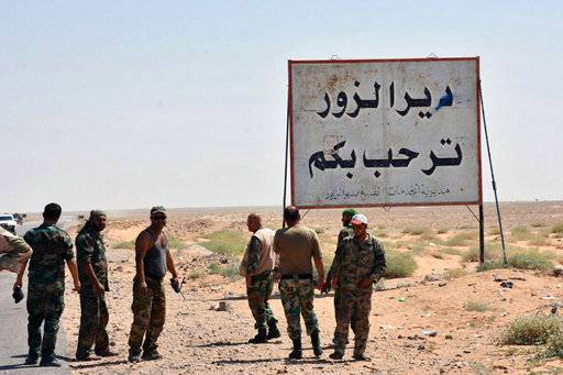 "FILE - This file photo released Sept. 3, 2017, by the Syrian official news agency SANA, shows Syrian troops and pro-government gunmen standing next to a sign in Arabic which reads, ""Deir el-Zour welcomes you,"" in the eastern city of Deir el-Zour, Syria. Syrian state media say the army has liberated the eastern city of Deir el-Zour from the Islamic State group. Friday's report says the military is now in full control of the long contested city. (SANA via AP, File)"