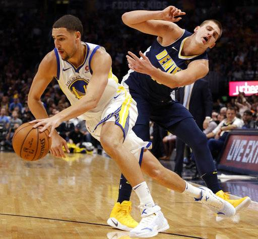 Golden State Warriors guard Klay Thompson (11) drives past Denver Nuggets center Nikola Jokic (15) during the second quarter of an NBA basketball game Saturday, Nov. 4, 2017, in Denver. (Photo by Jack Dempsey)