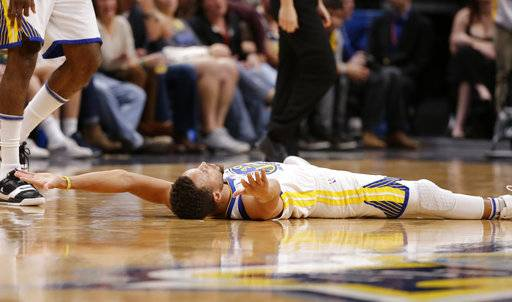 Golden State Warriors guard Stephen Curry lies on the court after hitting a three-point basket and drawing a foul during the third quarter of an NBA basketball game against the Denver Nuggets, Saturday, Nov. 4, 2017, in Denver. (Photo by Jack Dempsey)