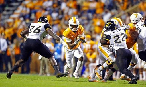 Tennessee running back John Kelly (4) runs for yardage as he's defended by Southern Mississippi linebacker Jeremy Sangster (26) in the first half of an NCAA college football game Saturday, Nov. 4, 2017, in Knoxville, Tenn.