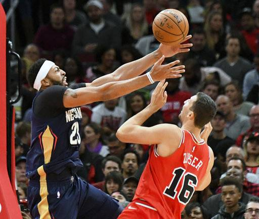 New Orleans Pelicans forward Anthony Davis (23) and Chicago Bulls forward Paul Zipser (16) go for the ball during the first half of an NBA basketball game, Saturday, Nov. 4, 2017, in Chicago.