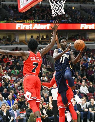 New Orleans Pelicans guard Jrue Holiday (11) looks to pass the ball around Chicago Bulls guard Justin Holiday (7) during the first half of an NBA basketball game, Saturday, Nov. 4, 2017, in Chicago.