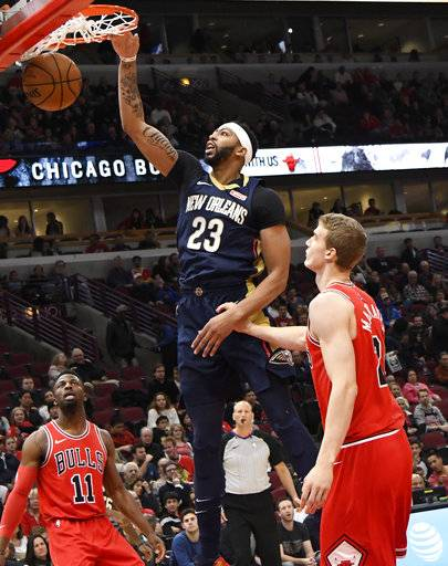 New Orleans Pelicans forward Anthony Davis (23) dunks the ball as Chicago Bulls guard David Nwaba (11) and forward Lauri Markkanen (24) watch during the first half of an NBA basketball game, Saturday, Nov. 4, 2017, in Chicago.