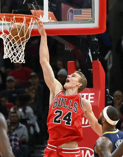 Chicago Bulls forward Lauri Markkanen (24) dunks the ball as New Orleans Pelicans center DeMarcus Cousins (0) watches during the first half of an NBA basketball game, Saturday, Nov. 4, 2017, in Chicago.