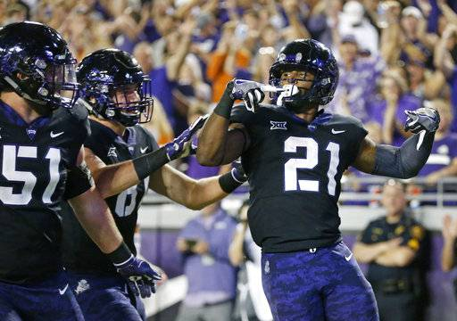 TCU running back Kyle Hicks (21) celebrates with teammates including guard Austin Schlottmann (51) after scoring a touchdown against Texas during the first half of an NCAA college football game Saturday, Nov. 4, 2017, in Fort Worth, Texas.