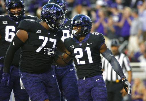 TCU's Lucas Niang (77) and running back Kyle Hicks (21) celebrate Hicks' touchdown during the first half of an NCAA college football game against Texas on Saturday, Nov. 4, 2017, in Fort Worth, Texas.