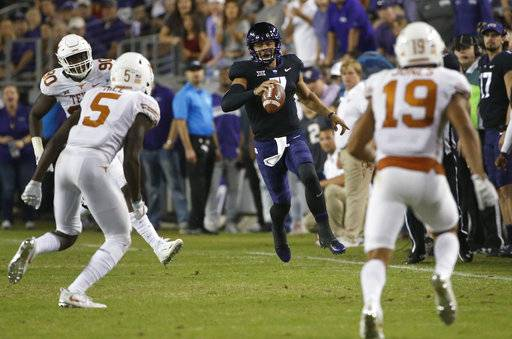 TCU quarterback Kenny Hill (7) runs for a first down as Texas defenders Holton Hill (5) and Brandon Jones (19) close in during the first half of an NCAA college football game Saturday, Nov. 4, 2017, in Fort Worth, Texas.