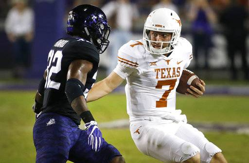 Texas quarterback Shane Buechele (7) is pursued by TCU linebacker Travin Howard (32) during the first half of an NCAA college football game Saturday, Nov. 4, 2017, in Fort Worth, Texas.