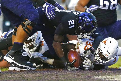 TCU running back Kyle Hicks (21) takes the ball into the end zone to score a touchdown as Texas linebacker Gary Johnson (33) defends during the first half of an NCAA college football game Saturday, Nov. 4, 2017, in Fort Worth, Texas.