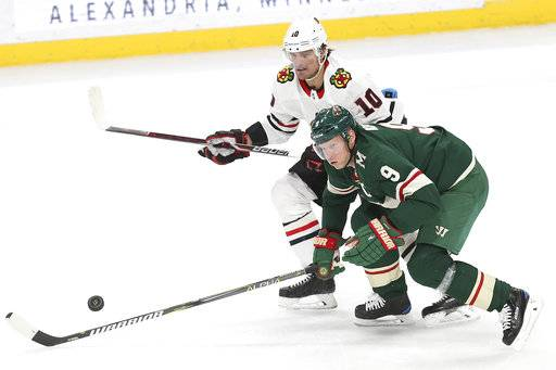 Minnesota Wild's Mikko Koivu (9) and Chicago Blackhawks' Patrick Sharp (10) look toward a loose puck in the first period of an NHL hockey game Saturday, Nov. 4, 2017, in St. Paul, Minn. AP Photo/Stacy Bengs)