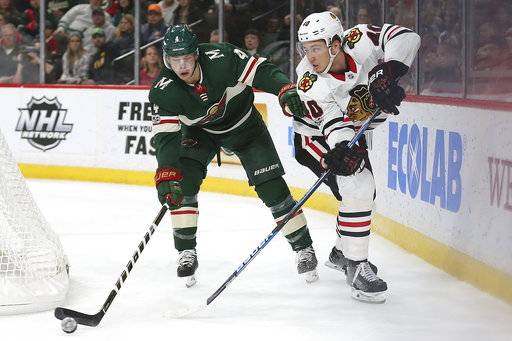 Chicago Blackhawks' John Hayden (40) passes the puck away from Minnesota Wild's Mike Reilly (4) in the second period of an NHL hockey game Saturday, Nov. 4, 2017, in St. Paul, Minn. AP Photo/Stacy Bengs)