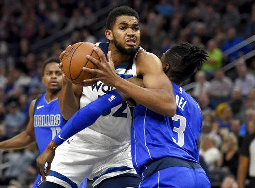 Minnesota Timberwolves center Karl-Anthony Towns (32) fouls Dallas Mavericks center Nerlens Noel (3) during the first quarter of an NBA basketball game on Saturday, Nov. 4, 2017, in Minneapolis.