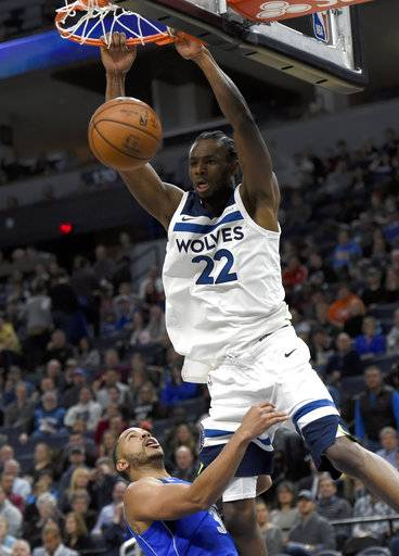 Minnesota Timberwolves forward Andrew Wiggins (22) dunks over Dallas Mavericks guard Devin Harris (34) during the first half of an NBA basketball game on Saturday, Nov. 4, 2017, in Minneapolis. The Timberwolves won 112-99.