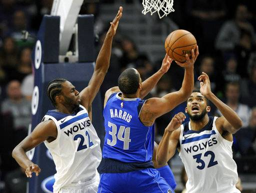 Minnesota Timberwolves forward Andrew Wiggins (22) and center Karl-Anthony Towns (32) guard against a shot by Dallas Mavericks guard Devin Harris (34) during the first half of an NBA basketball game on Saturday, Nov. 4, 2017, in Minneapolis. The Timberwolves won 112-99.