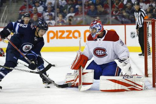 Winnipeg Jets' Brandon Tanev (13) attempts to get the puck past Montreal Canadiens goaltender Al Montoya (35) during second-period NHL hockey game action in Winnipeg, Saturday, Nov. 4, 2017. (John Woods/The Canadian Press via AP)