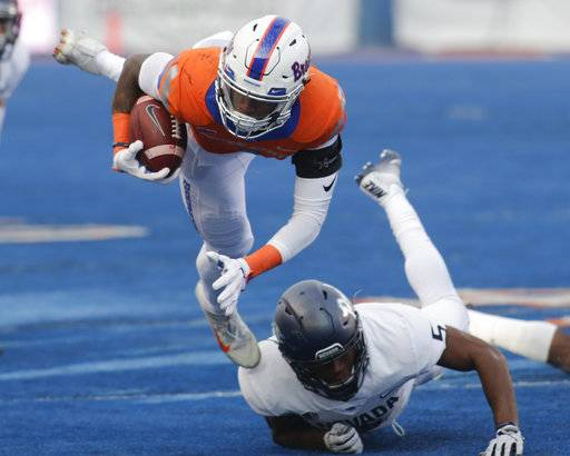 Boise State wide receiver Cedrick Wilson is upended by Nevada defensive back Dameon Baber during the first half of an NCAA college football game in Boise, Idaho, Saturday, Nov. 4, 2017.