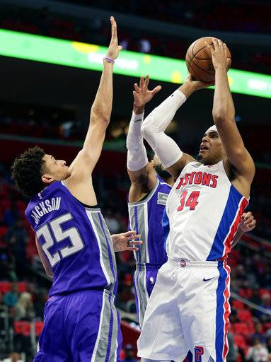 Detroit Pistons forward Tobias Harris (34) takes a shot against Sacramento Kings forward Justin Jackson (25) and guard Garrett Temple, center, during the first half of an NBA basketball game Saturday, Nov. 4, 2017, in Detroit.