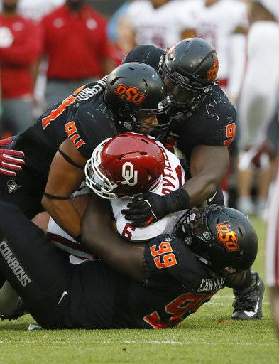 Oklahoma quarterback Baker Mayfield (6) is sacked by a number of Oklahoma State defenders in the second half of an NCAA college football game in Stillwater, Okla., Saturday, Nov. 4, 2017. Oklahoma won 62-52.