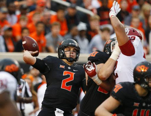Oklahoma State quarterback Mason Rudolph (2) passes under pressure in the second half of an NCAA college football game against Oklahoma in Stillwater, Okla., Saturday, Nov. 4, 2017. Oklahoma won 62-52.