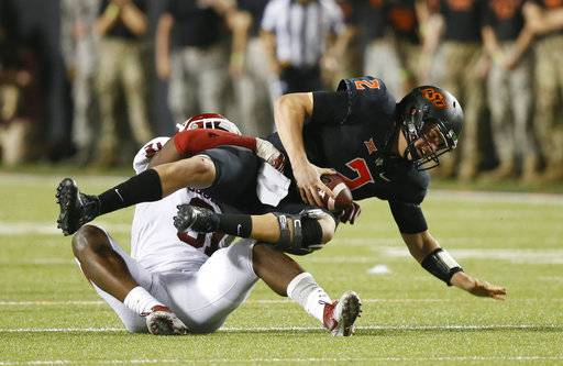 Oklahoma State quarterback Mason Rudolph (2) is sacked by Oklahoma defensive end Ogbonnia Okoronkwo, left, in the second half of an NCAA college football game in Stillwater, Okla., Saturday, Nov. 4, 2017. Oklahoma won 62-52.