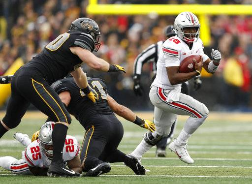 Ohio State quarterback J.T. Barrett (16) runs from Iowa defensive end Parker Hesse, left, during the first half of an NCAA college football game, Saturday, Nov. 4, 2017, in Iowa City, Iowa.