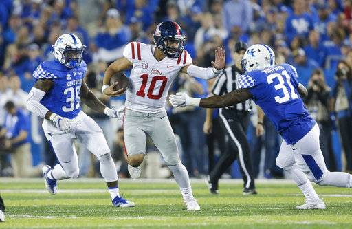 Mississippi quarterback Jordan Ta'amu (10) looks for room to run between Kentucky defensive end Denzil Ware, left, and linebacker Jamar Watson during the second half of an NCAA college football game Saturday, Nov. 4, 2017, in Lexington, Ky.